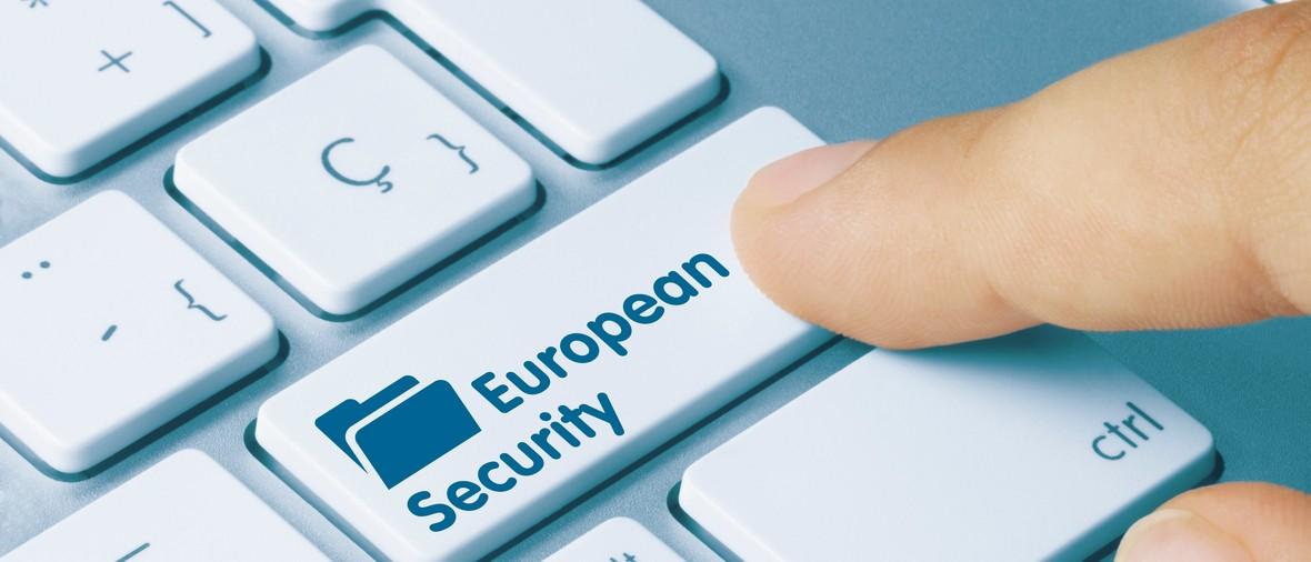 European Security Written on Blue Key of Metallic Keyboard. Finger pressing key.