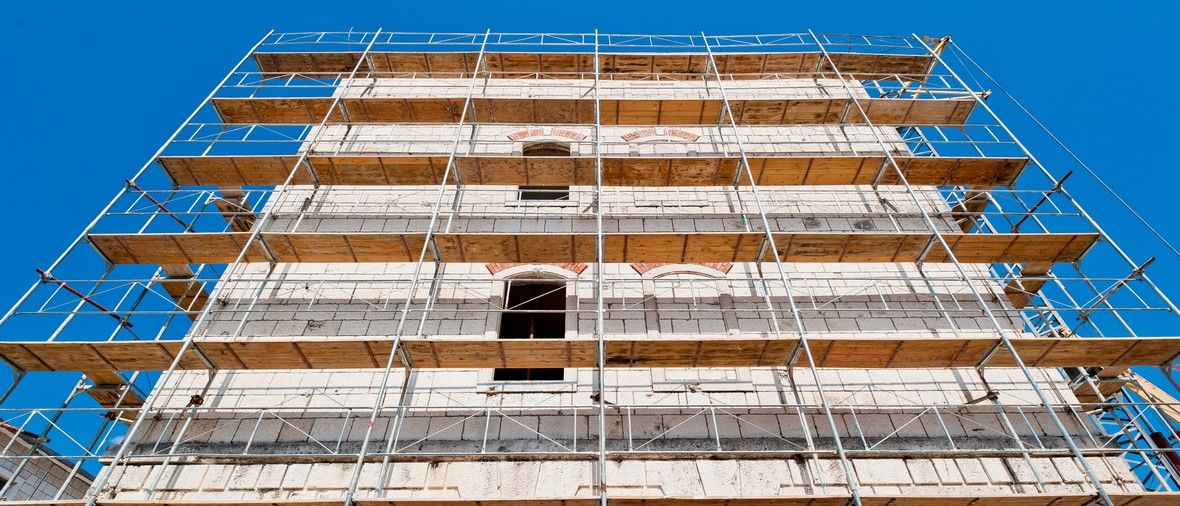 old building during reconstruction with wooden scaffolding viewed from below