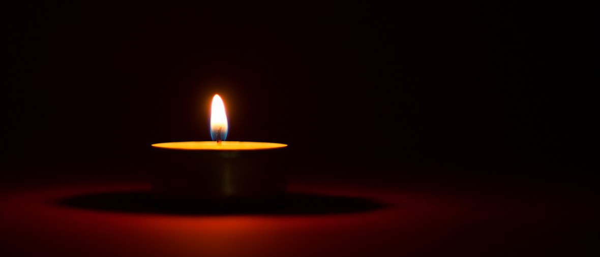 One candle burning in the dark, black and red background
